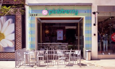 The outdoor seating area of a Pinkberry frozen yogurt shop on a bright, sunny day.