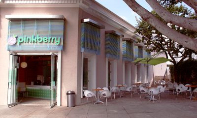 Exterior of a Pinkberry location with outdoor seating and a tree on a lovely, sunny day.