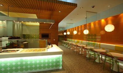 The interior of a fancy Pinkberry location with a counter on the left and seating on the right.