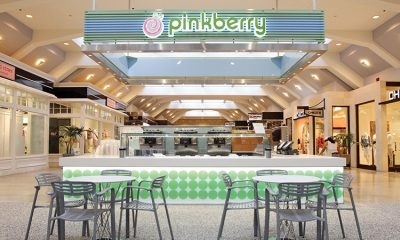 A Pinkberry kiosk in a shopping mall with bright lights and a seating area in front of the counter.