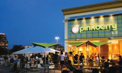A nighttime shot of a Pinkberry restaurant with many happy people mingling outside on the patio.